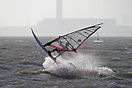 A brave windsurfer attempts flight.