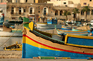 Traditional Maltese luzzu and the harbour of Marsaxlokk at sunset