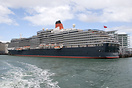 Queen Victoria on her maiden world cruise dwarfs the hotels in downtow...