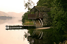 A boat house on the shore of a misty Ullswater in the Lake District