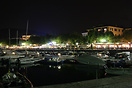 Boats and waterfront restaurants in a Lake Garda marina by night.