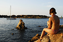 A girl watching a yacht entering Porto Cervo harbour on Sardinia's Cos...