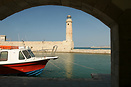 An archway in Chania harbour framing a tour boat the famous lighthouse...