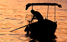 A crab fisherman in a traditional Maltese kajjik at sunrise in Marsamx...