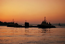 The submarine HMS Turbulant leaves Plymouth at sunset with a tug escor...